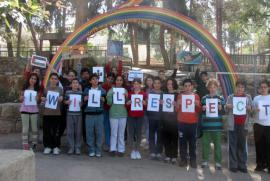 The children of Neve Shalom under a rainbow with the flags of the two nations