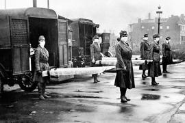 Women holding stretchers at the backs of ambulances during the global flu epidemic, St Louis, Missouri, October 1918.