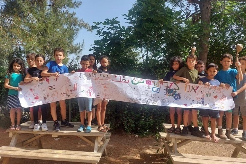 """Children in Neve Shalom - Wahat al-Salam's primary school. The sign, written in Arab and Hebrew, says """"We ask for peace, to live safely and equally"""""""
