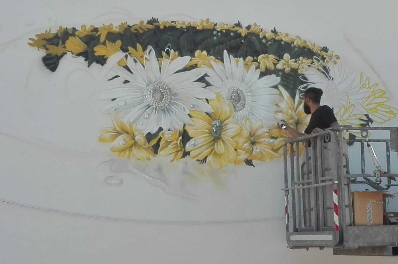 The artist Neve works on the murals in Piave Square