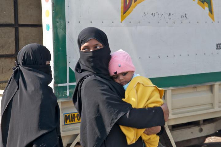 Veiled women walking with their children